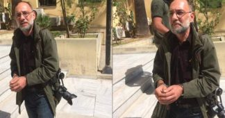 Police handcuffs, arrests photojournalist Stamatiou during squat evacuation